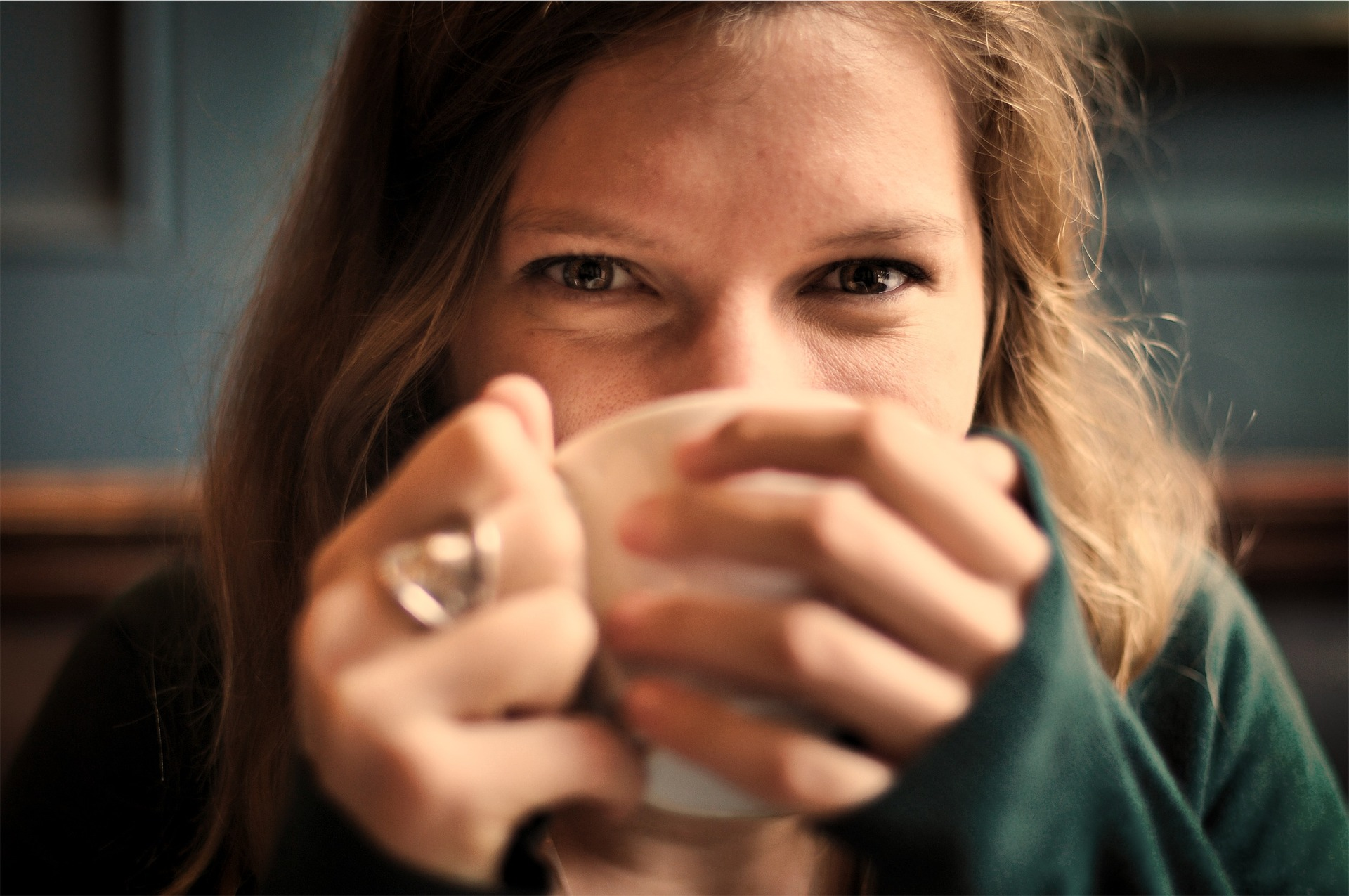 Woman drinking coffee with sparkling eyes